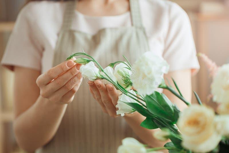 Het jonge beroep die van de vrouwenbloemist met bloemen werken stock afbeelding