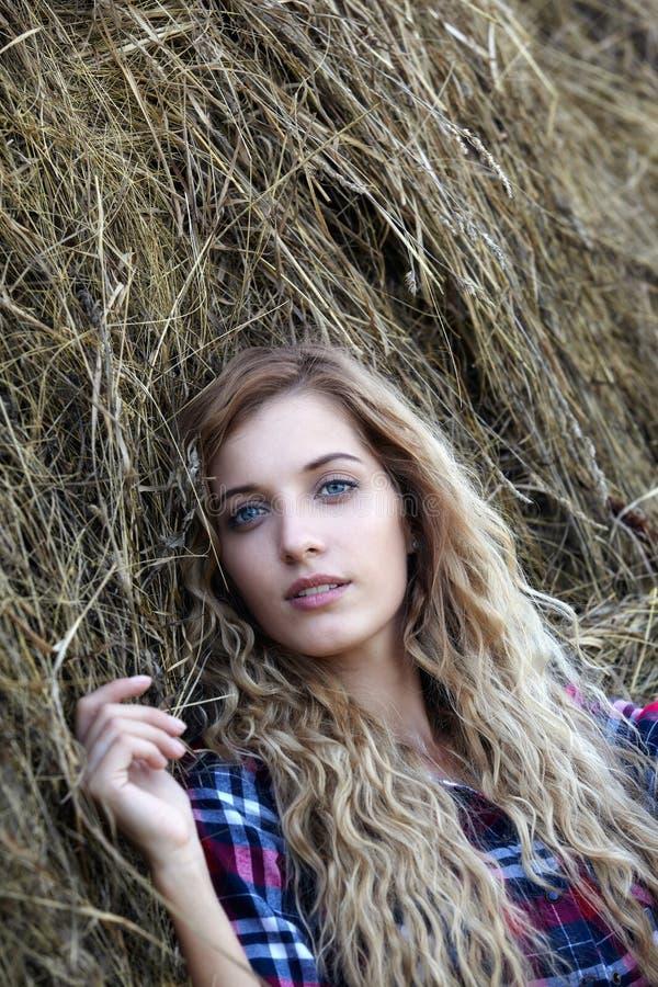 Het jonge blonde blauw-eyed meisje van het land dichtbij hooibergen royalty-vrije stock afbeeldingen