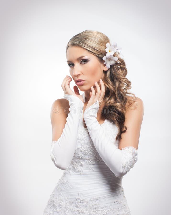 Het jonge blonde bruid stellen in mooie make-up stock afbeelding