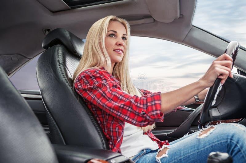Het jonge blonde drijft een auto royalty-vrije stock afbeeldingen