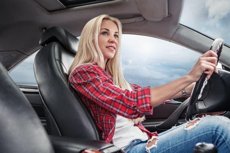 Het jonge blonde drijft een auto stock afbeelding