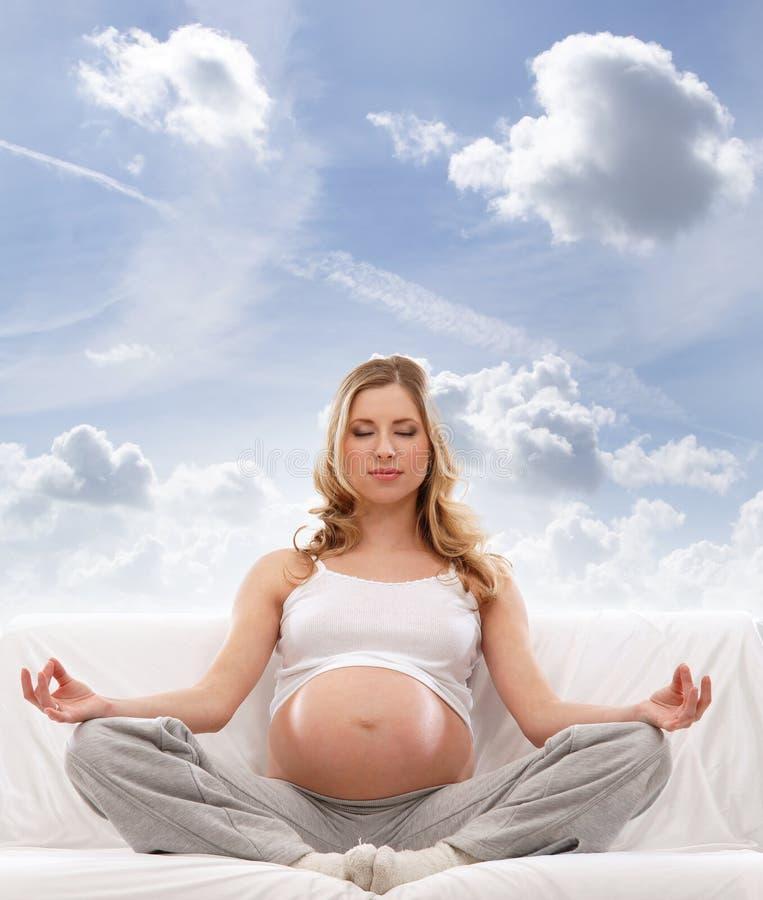 Het jonge blonde Kaukasische zwangere vrouw mediteren stock foto's