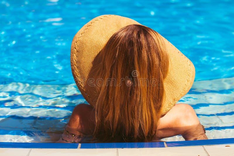 Het jonge blonde meisje heeft een rust bij de pool Achter mening zomer stock foto