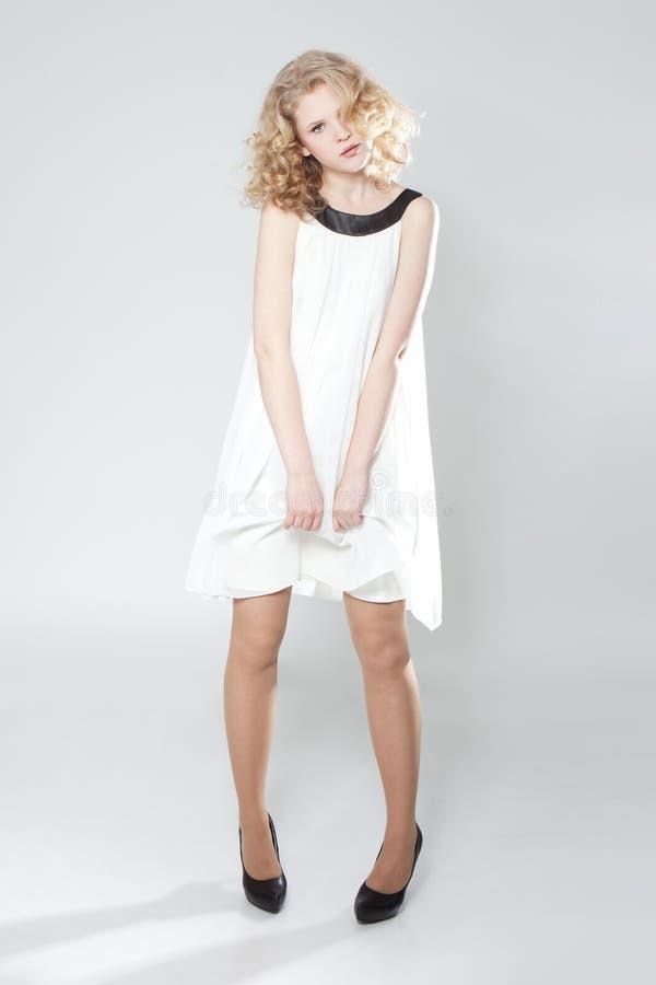 Het jonge blonde meisje stellen in studio in witte kleding royalty-vrije stock foto