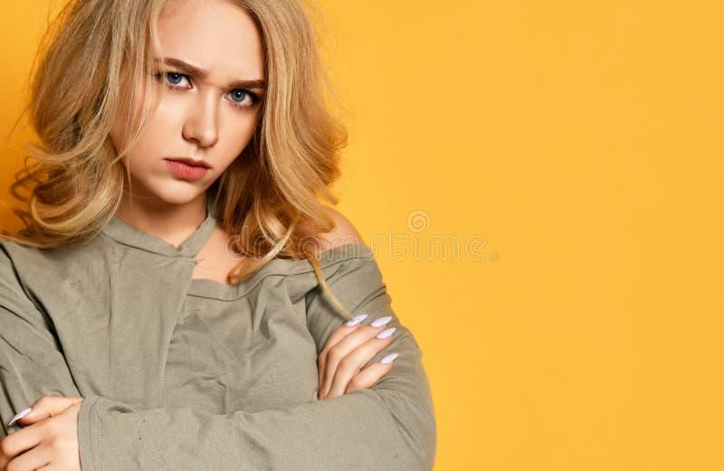 Het jonge blonde verstoorde meisje in korte blouse met gekruiste wapens is veel beledigd, kijkt boos en somedody schuld royalty-vrije stock fotografie