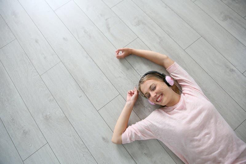 Het jonge blonde vrouw ontspannen op de vloer die aan muziek luisteren stock foto