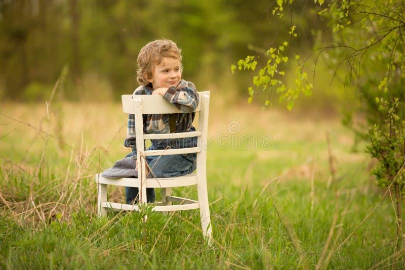 Het jonge blondejongen ontspannen op witte oude stoel in de lentelandschap stock afbeelding