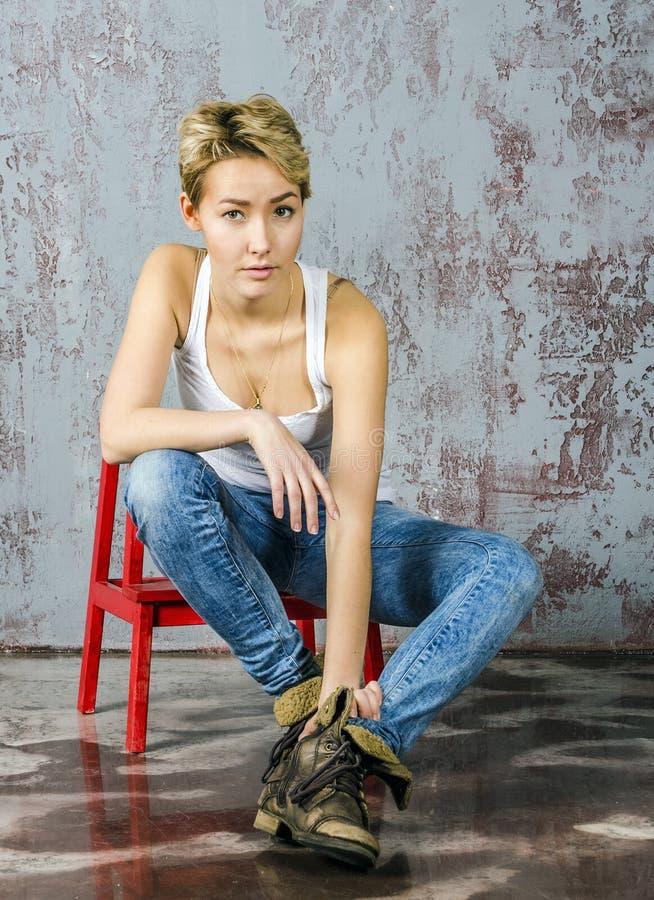 Het jonge blondemeisje met kort haar in een denimjasje en jeans zit en kijkt stock foto's