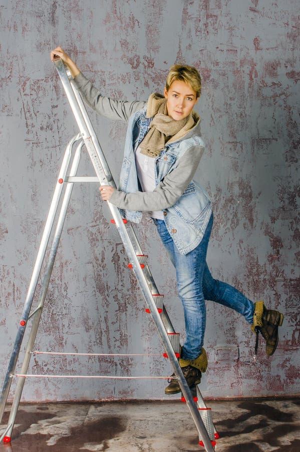 Het jonge blondemeisje met kort haar in een denimjasje en jeans zit en kijkt royalty-vrije stock foto