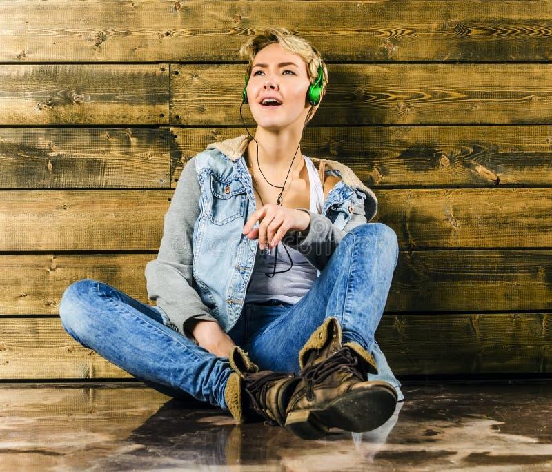 Het jonge blondemeisje met kort haar in een denimjasje en jeans zit en kijkt stock afbeelding