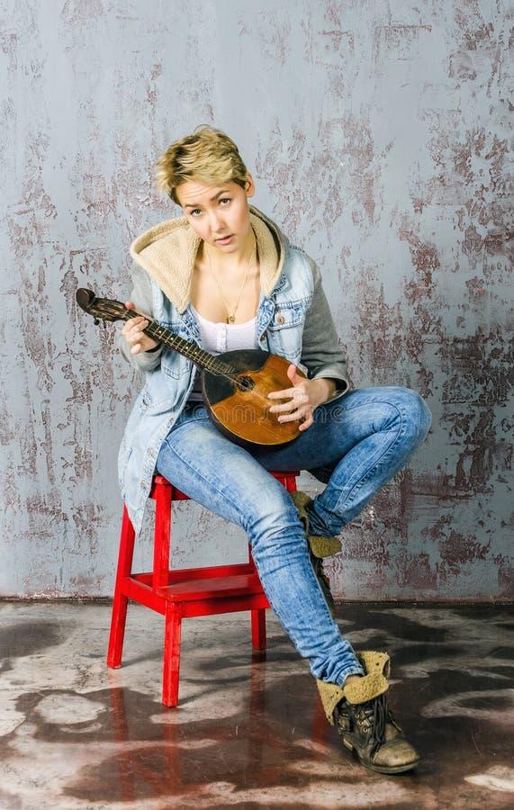 Het jonge blondemeisje met kort haar in een denimjasje en jeans zit en kijkt met dombra stock afbeelding