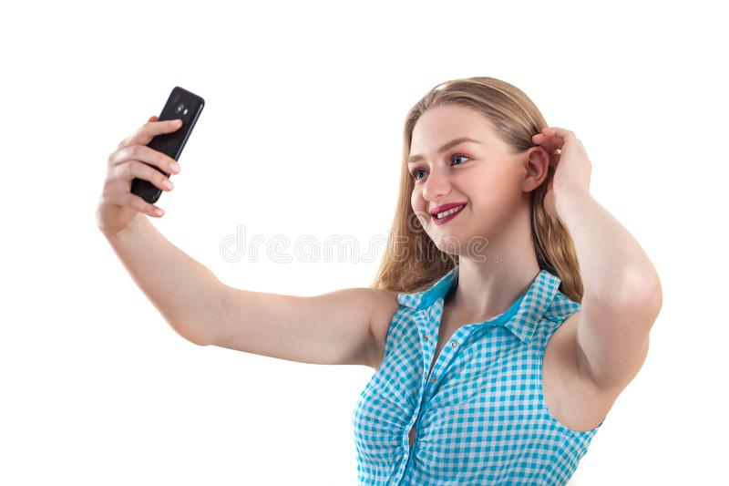Het jonge blondemeisje nemen selfie op een witte achtergrond, houdt smil royalty-vrije stock afbeeldingen