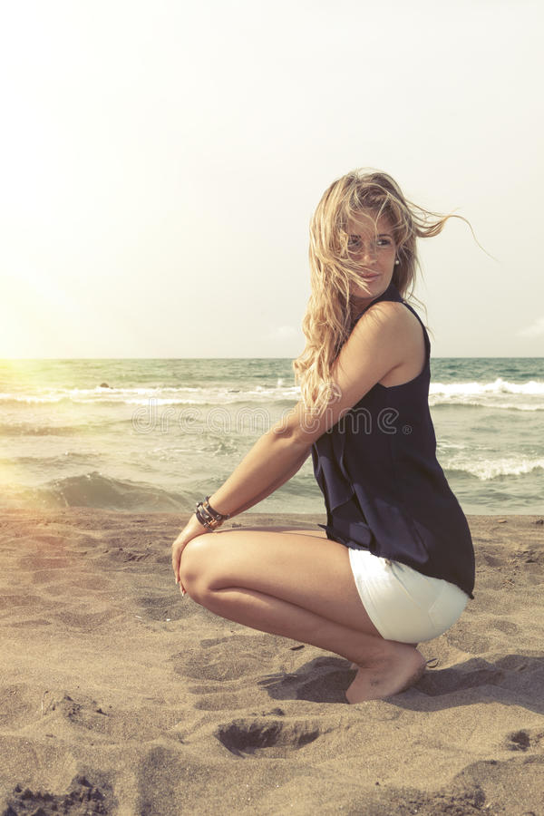 Het jonge blondemeisje ontspannen op het strandzand Wind in haar blond haar stock foto
