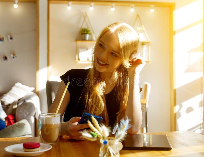 Het jonge blondemeisje van Europese verschijning in koffie glimlacht met sluwe glimlach, in de handen van een smartphone, op de l stock foto's