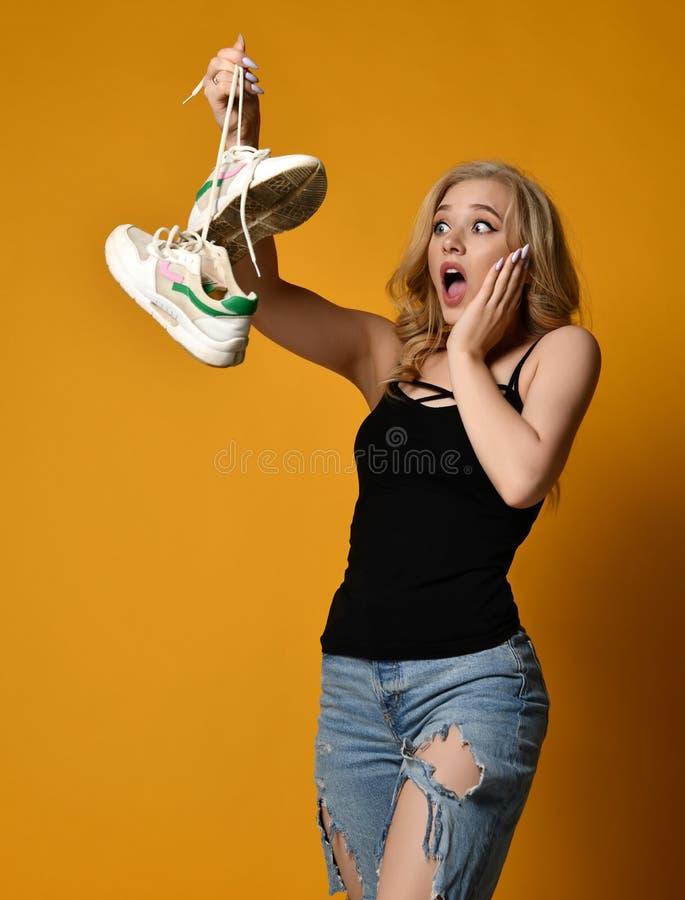Het jonge blondemeisje is zeer verrast en met afschuw vervuld door oud paar vuile schoenen die zij heeft gevonden stock fotografie