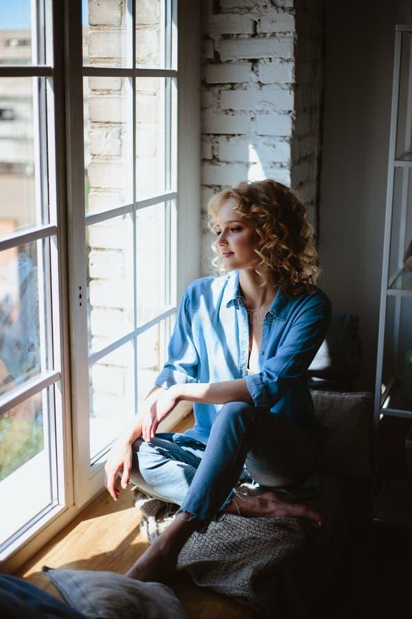 Het jonge blondevrouw koelen dichtbij panoramisch venster in haar woonkamer, zonnig weer stock afbeelding