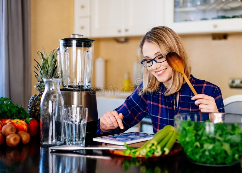 Het jonge blondevrouw koken in keuken royalty-vrije stock foto's