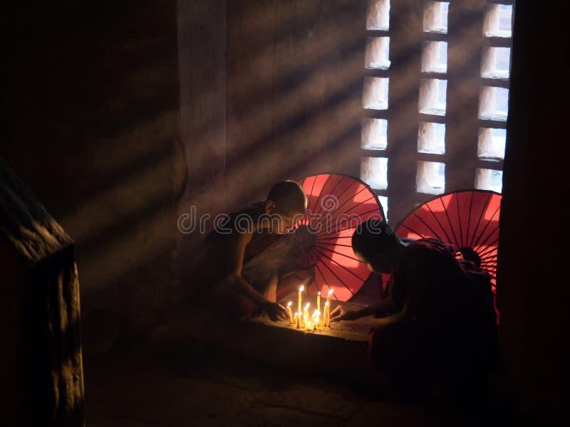 Het jonge Boeddhistische bidden met kaarsen in pagode royalty-vrije stock foto
