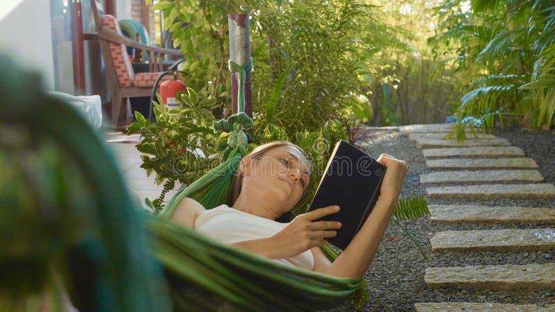 Het jonge boek die van de vrouwenlezing in hangmat op terras liggen stock afbeeldingen