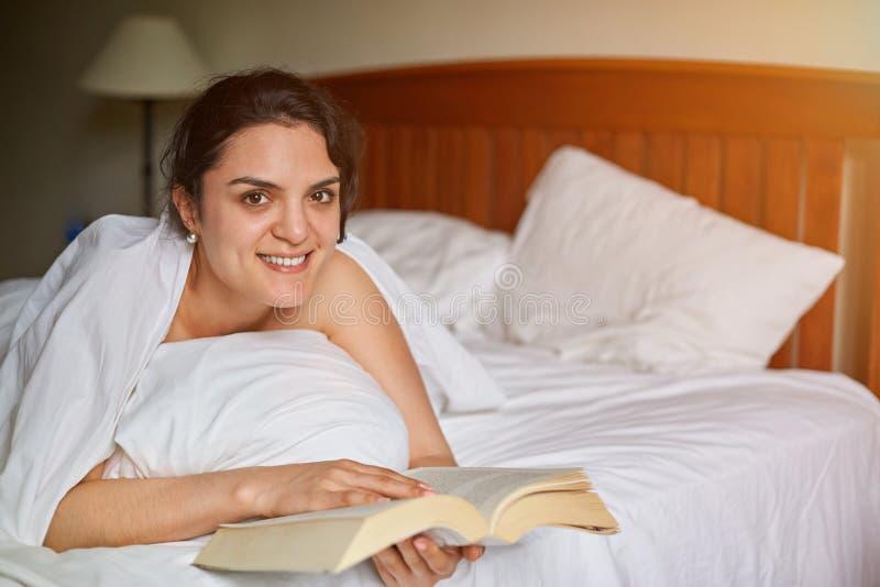Het jonge boek van de vrouwenlezing in bed stock foto