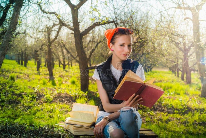 Het jonge boek van de vrouwenlezing in het park stock afbeelding