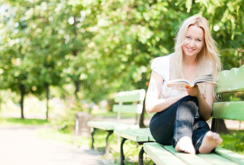 Het jonge boek van de vrouwenlezing in park stock fotografie