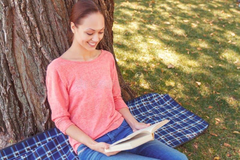 Het jonge boek van de vrouwenlezing in park royalty-vrije stock afbeeldingen