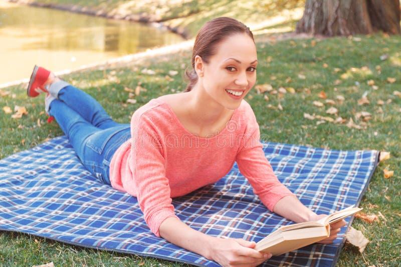 Het jonge boek van de vrouwenlezing in park stock afbeelding