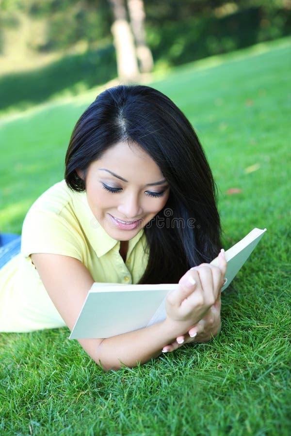 Het jonge boek van de vrouwenlezing in park stock foto's