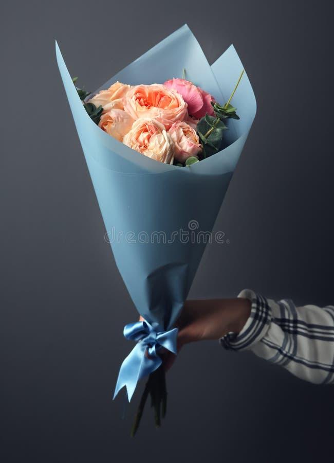 Het jonge boeket van de vrouwenholding van mooie bloemen op grijze achtergrond royalty-vrije stock fotografie