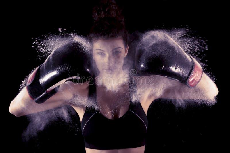 Het jonge boksermeisje slaat omhoog zijn handschoenen stock foto