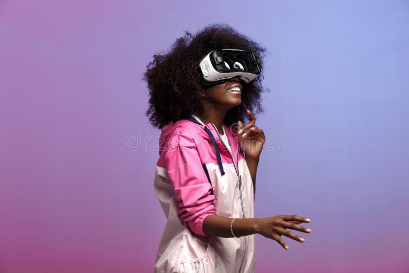 Het jonge bruin-haired krullende meisje van mod. gekleed in de roze blazer gebruikt de virtuele werkelijkheidsglazen in de studio stock fotografie