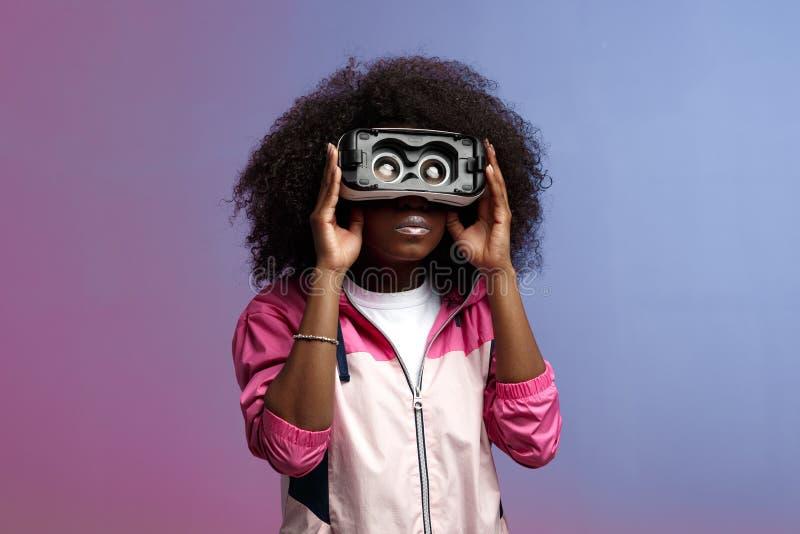 Het jonge bruin-haired krullende meisje van mod. gekleed in de roze blazer gebruikt de virtuele werkelijkheidsglazen in de studio stock afbeelding