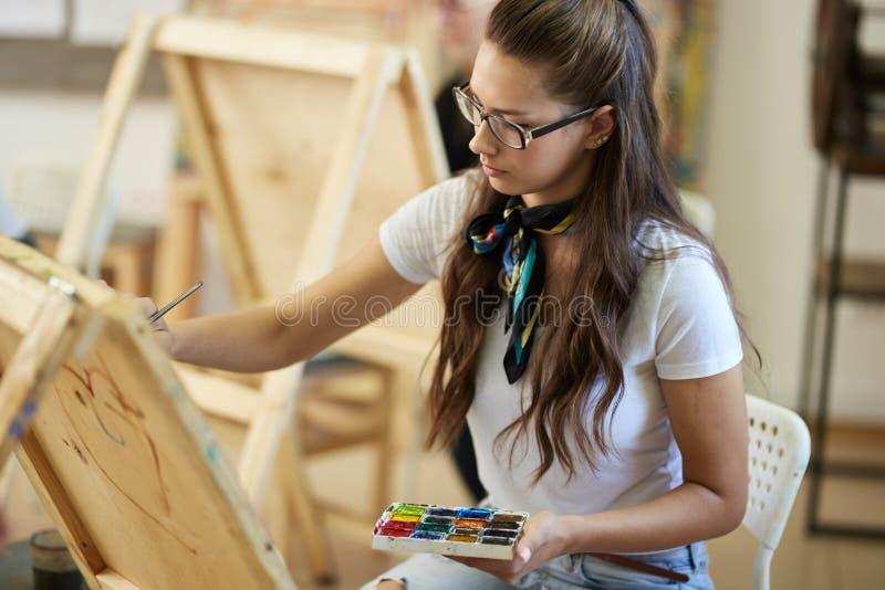 Het jonge bruin-haired meisje in glazen gekleed in witte t-shirt en jeans met een sjaal rond haar hals schildert binnen een beeld royalty-vrije stock afbeeldingen