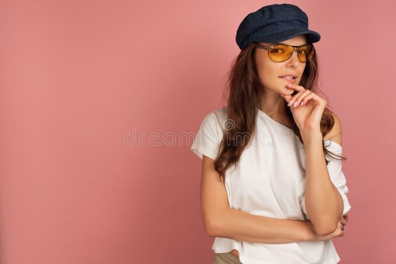 Het jonge brunette bijt haar lip zorgvuldig bekijkend de camera stock fotografie