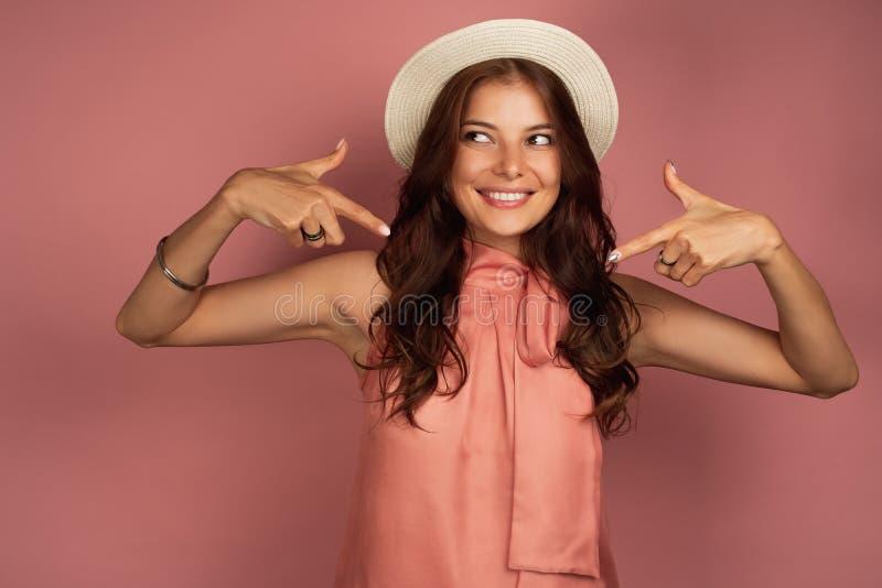 Het jonge brunette die een hoed dragen richt op zich met een glimlach, roze achtergrond royalty-vrije stock afbeeldingen