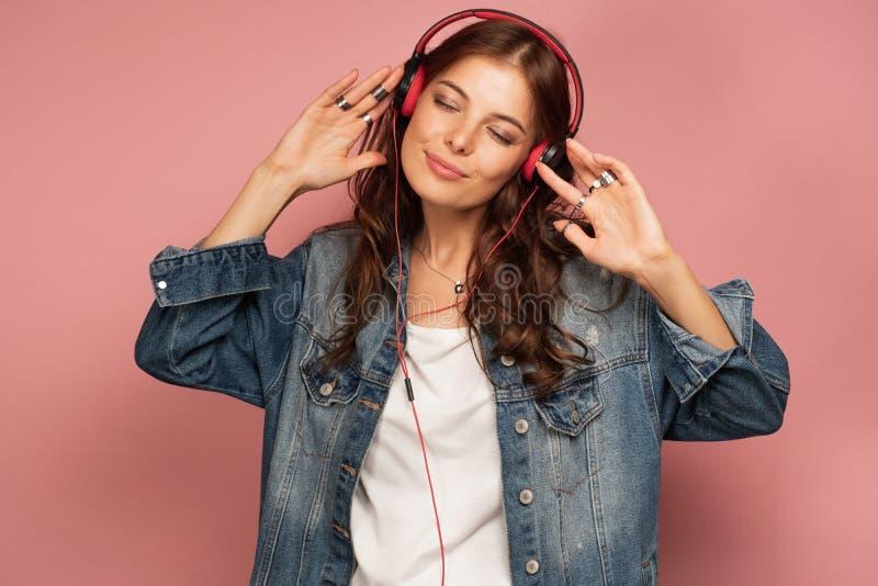Het jonge brunette in een grote jeanslaag luistert aan muziek in haar hoofdtelefoons met haar gesloten ogen stock afbeeldingen