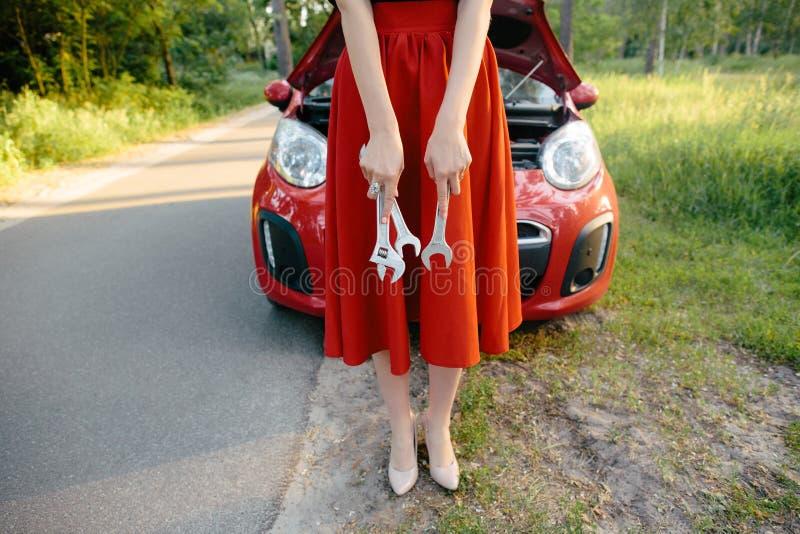 Het jonge brunette in een kleding herstelt een rode auto met een moersleutel royalty-vrije stock afbeelding