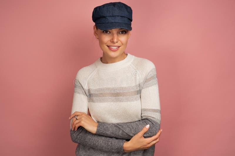 Het jonge brunette in een trui en een blauw GLB glimlacht bij de camera, roze achtergrond royalty-vrije stock fotografie