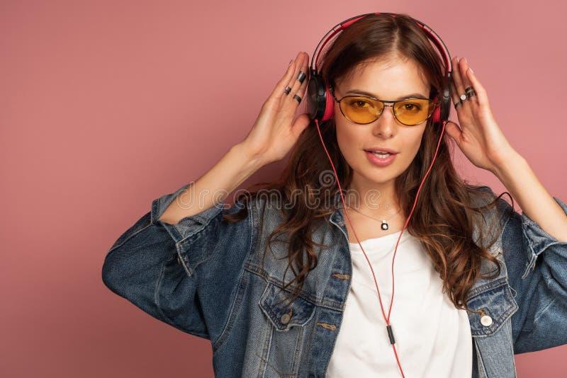 Het jonge brunette in gele oogglazen luistert aan muziek in haar hoofdtelefoons, roze achtergrond royalty-vrije stock foto