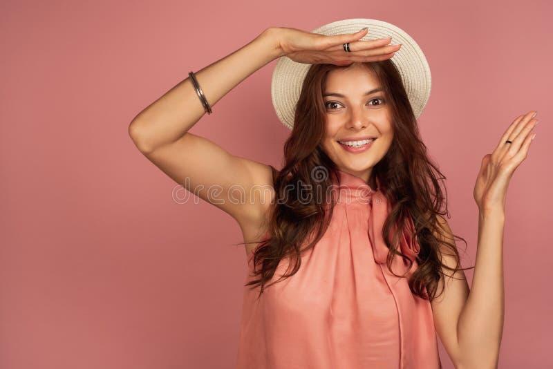 Het jonge brunette glimlacht en kijkt ver weg houdend haar hand boven haar voorhoofd, roze achtergrond stock fotografie