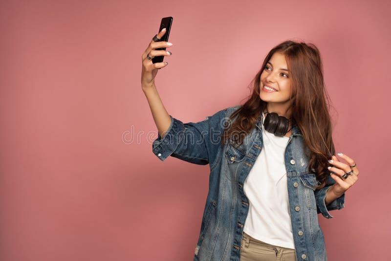 Het jonge brunette neemt een selfie op haar smartphone glimlachend over roze achtergrond royalty-vrije stock afbeeldingen