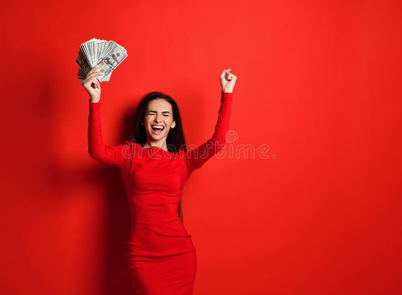 Het jonge brutale brunette in een rode kleding verheugt zich in een hoop van geld in haar handen die zij heeft gewonnen royalty-vrije stock foto