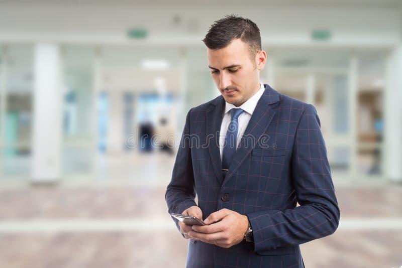 Het jonge bussinesman of manager texting op smartphone stock fotografie