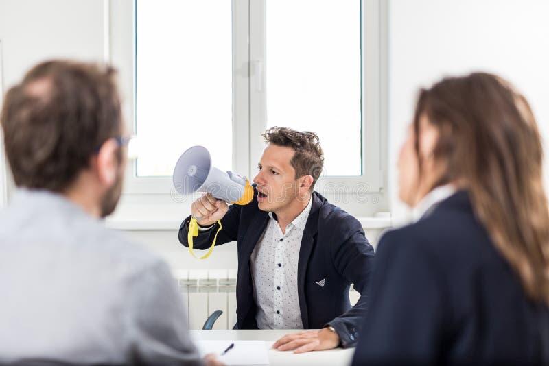 Het jonge chef- schreeuwen bij werknemers door megafoon in conferentieruimte stock afbeeldingen
