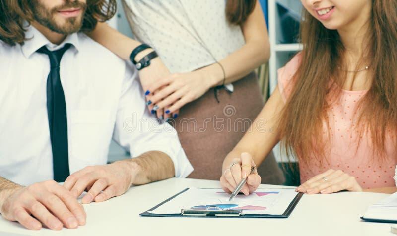 Het jonge commerciële team analise financiële document grafieken en grafieken op de lijst Het schaak stelt bischoppen voor stock afbeelding