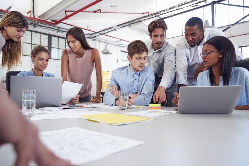 Het jonge commerciële team verzamelde rond twee laptops in een bureau stock afbeeldingen