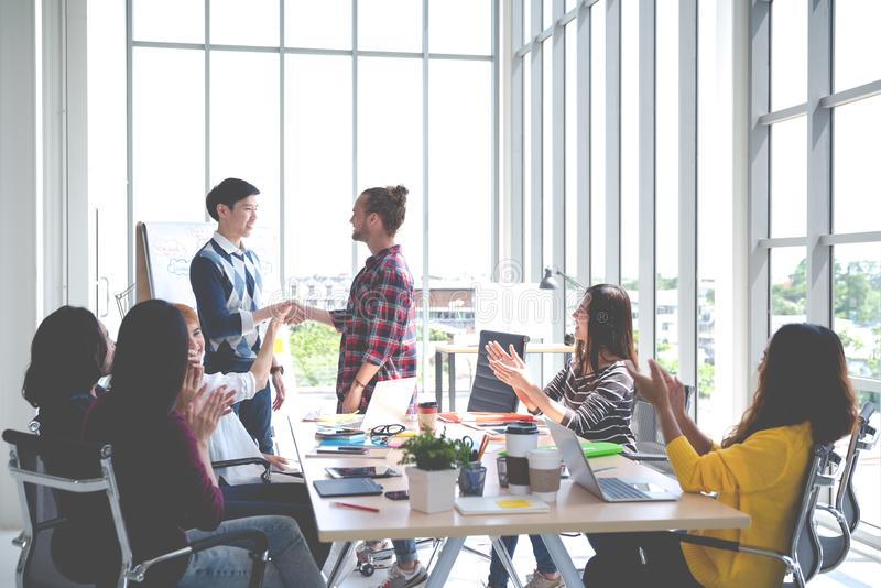 Het jonge creatieve gelukkige warme onthaal van het ontwerp Aziatische team aan nieuwe coworkwerknemer in het samenkomen of oplei stock afbeeldingen