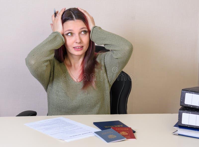 Het jonge creatieve meisje clutched bij zijn hoofd vullend het arbeidsovereenkomst en werkgelegenheidsverslag, paspoort en diplom stock afbeelding