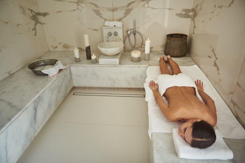 Het jonge dame ontspannen in het Turkse bad terwijl het liggen op haar maag royalty-vrije stock afbeelding